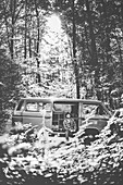 Man sitting in front of a VW Bus in the forest, Aalen, Ostalbkreis, Baden-Württemberg, germany, europe.