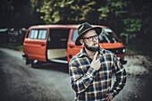 Mann steht vor VW Bus im Wald mit einer Pfeife, Aalen, Ostalbkreis, Baden-Württemberg, Deutschland, Europa.