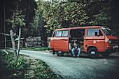 Mann sitzt vor VW Bus im Wald mit einer Kaffeemühle, Aalen, Ostalbkreis, Baden-Württemberg, Deutschland, Europa.