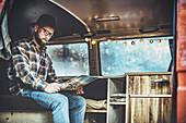 Mann sitzt in VW Bus mit Landkarte, Aalen, Ostalbkreis, Baden-Württemberg, Deutschland, Europa.