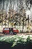 Mann sitzt vor VW Bus im Wald, Aalen, Ostalbkreis, Baden-Württemberg, Deutschland, Europa.