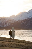 Surfer Standing With His Surfboard At Kachemak Bay, Homer Spit, Southcentral Alaska, USA