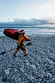 Kayak surfer carrying a paddle and kayak in winter along the snow covered shore, Homer, Southcentral Alaska, USA