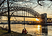 Couple Enjoying Sunset Near Hell Gate And Rfk Triboro Bridges, Ralph Demarco Park; Queens, New York, United States Of America