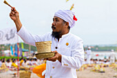 A Religious Man Sprinkles Water On Local Balinese People At A Ceremony At The Beach; Bali