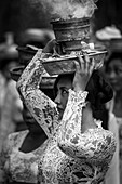 A Young Woman At A Religious Ceremony Carrying A Smoking Offering On Her Head; Bali, Indonesia