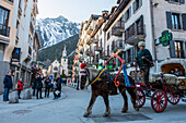 Tourists Ride In A Buggy Pulled By A Horse Through The Streets; Chamonix, France