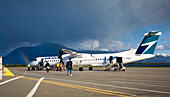 Rainbow Over The Terrace Kitimat Airport As Passengers Load A Plane On The Tarmac; Terrace, British Columbia, Canada