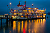 Lights illuminating a river boat docked on the Columbia River at dusk; Astoria, Oregon, United States of America