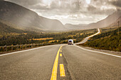 A vehicle with trailer heads down a road leading through fields and mountains under a cloudy sky; Newfoundland, Canada