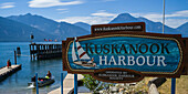 A sign for Kuskanook Harbour on Kootenay Lakewith people on a dock and in a boat in the background; Creston, British Columbia, Canada