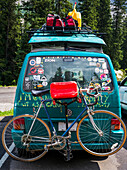A camper van in a parking lot covered with bumper stickers and graffiti, and with a luggage on a rack and bike on the back; Field, Alberta, Canada