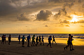 Runners race on the beach at sunrise during the 2017 USA Beach Running Championships; Cocoa Beach, Florida, United States of America