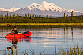 A man paddles a pack raft across Donnelly Lake with Mt. Hayes towering in the distance; Alaska, United States of America
