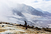 A man looks toward Trident Volcano through clouds while ascending the Knife Creek Glaciers in Katmai National Park; Alaska, United States of America