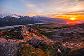 A man observes a tranquil sunset from an alpine perch high above the Delta River in the Alaska Range; Alaska, United States of America