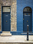 Two residential doorways side by side, one numbered eleven and the other eleven and a half, with differing facade and windows for each; London, England