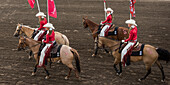 Cowgirls in red and white riding horses and carrying flags at the Calgary Stampede; Calgary, Alberta, Canada