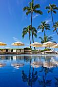 Halekalani Pool at Waikiki with palm trees and umbrellas reflected in the water; Honolulu, Oahu, Hawaii, United States of America