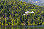 A float plane travels low above the ocean on a scenic tour of the forest and mountains near Vancouver; British Columbia, Canada