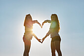 Two teenage girls stand making the shape of a heart with their arms as the sunlight shines through, Woodbine Beach; Toronto, Ontario, Canada