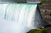 Close-up of Niagara Falls with cliffs and tourists standing on the viewing platforms; Niagara Falls, Ontario, Canada