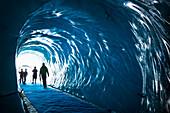 Family of tourists step into ice cave under Mer de Glace Glacier; Chamonix-Mont-Blanc, Haute-Savoie, France