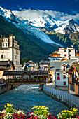 Mont Blanc over Chamonix town and L'Arve River with flowers; Chamonix-Mont-Blanc, Haute-Savoie, France