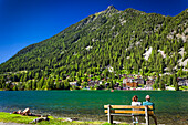 A couple enjoys the view on a bench at Champex Lake shore under blue sky, mountain and resorts are in the background; Champex, Valais, Switzerland