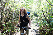 A Woman Stands On A Path In A Forest With Her Bicycle And A Backpack; Alaska, United States Of America