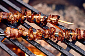Bacon Skewers Cooking Over A Flame On A Grill; Ontario, Canada