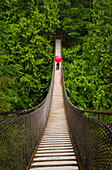 Woman With A Red Heart-Shaped Umbrella Crossing The Lynn Canyon Suspension Bridge, North Vancouver; Vancouver, British Columbia, Canada
