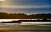 Silhouette Of A Couple And Their Bikes On Mackenzie Beach At Sunset; Tofino, British Columbia, Canada