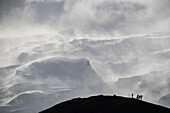 Group Of Photographers Silhouetted Against The Snow Laden Mountain; Iceland
