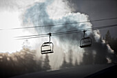 Silhouette of a chairlift on a ski hill with man made snow from  snow gun backlit by the sunlight, Copper Mountain Resort; Colorado, United States of America