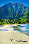 A surfboard sits on the beach at the water's edge with rugged green mountains and lush foliage on the island of Kauai; Hanalei, Kauai, Hawaii, United States of America