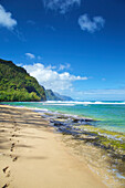 Footprints in the sand along the water's edge on the coastline of the Island of Hawaii; Haena, Island of Hawaii, Hawaii, United States of America