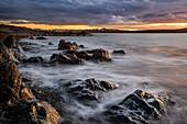 The rugged Atlantic coastline at sunrise under a cloudy sky; Bonavista, Newfoundland, Canada