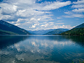 The blue sky and cloud reflected in the tranquil water of Kootenay Lake in the Selkirk Mountains; Nelson, British Columbia, Canada