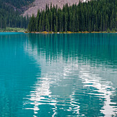 The stunning blue water of Moraine Lake with a forest along the shoreline reflected in the tranquil water in Banff National Park; Lake Louise, Alberta, Canada