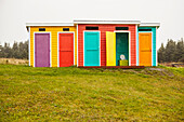Colourful buildings for bathrooms and change rooms with multi-coloured siding and doors on grass; Newfoundland, Canada