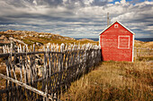 A small red shed beside a wooden picket fence along the coast; Newfoundland, Canada