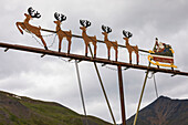 This out-of-place decorative scene of Santa Claus with his reindeer sleigh is attached to a light post at the Alaska DOT Chandalar Maintenance Camp along the Dalton Highway; Alaska, United States of America