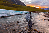 A backpacker observes the midnight sun peeking through the clouds from an unnamed fork of the Atigun River still partially covered in aufeis (sheet-like ice formations) in a remote valley of the Brooks Range; Alaska, United States of America