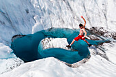 A man jumps onto an island of ice on Root Glacier in Wrangell-St. Elias National Park; Alaska, United States of America
