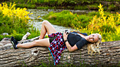 Portrait of a young woman with long blond hair laying on a log in a park holding a camera; Edmonton, Alberta, Canada