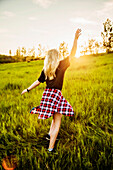 A young woman with long blond hair twirls and runs freely in a grass field in a park at sunset; Edmonton, Alberta, Canada