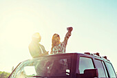 Young couple taking self-portraits with a cell phone while standing up in their sunroof of their vehicle; Edmonton, Alberta, Canada
