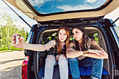 Two young women on a road trip sit in the back of a vehicle taking a self-portrait with a smart phone; Edmonton, Alberta, Canada