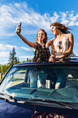 Two young women on a road trip stand up in the sunroof of a vehicle taking a self-portrait with a smart phone; Edmonton, Alberta, Canada